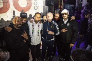 Chuck D from Public Enemy stands for a pic with Cypress Hill, as the 2018 bud logo looms over their right shoulders, and the bud.com founders stand off to their left
